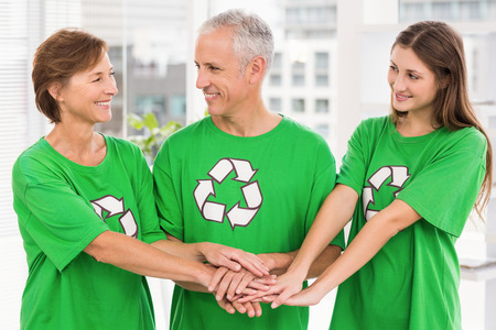 environmental friendly: Smiling eco-minded colleagues putting hands together in the office