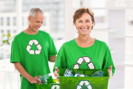 new business problems: Portrait of smiling eco-minded woman holding recycling box in the office Stock Photo