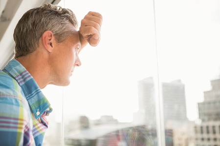 troubled: Troubled casual businessman leaning against window in the office