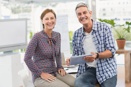 business casual: Portrait of smiling casual business colleagues with tablet in the office