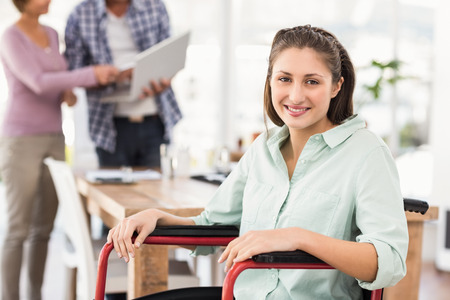 silla de ruedas: Portrait of smiling casual businesswoman in wheelchair in the office