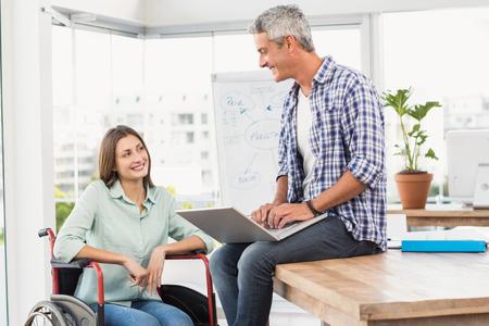 paraplegico: Empresaria ocasional en silla de ruedas hablando con su colega en la oficina Foto de archivo