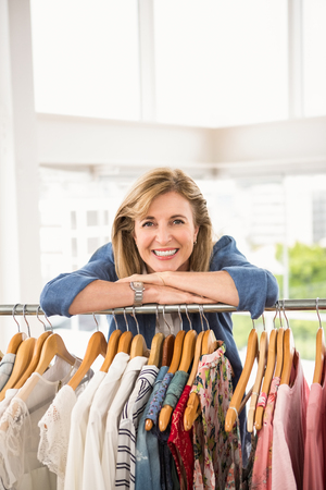 clothes rail: Portrait of smiling woman leaning on clothes rail in clothing store