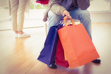 clothing store: Man waiting for his shopping woman in clothing store Stock Photo