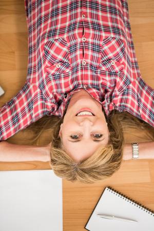 articulos de oficina: Retrato de mujer sonriente acostado en el piso rodeado de art�culos de oficina Foto de archivo