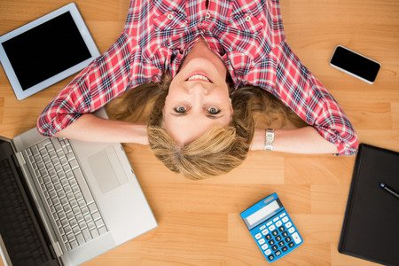 articulos de oficina: Retrato de mujer sonriente acostado en el piso rodeado de artículos de oficina Foto de archivo