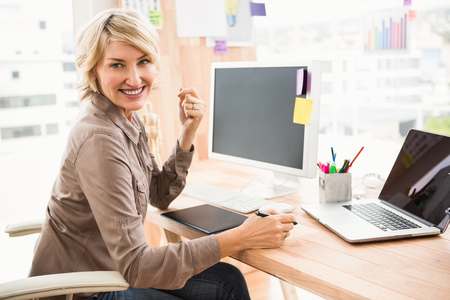 caucasians: Portrait of smiling casual designer sitting at desk in the office