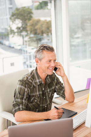 Smiling casual businessman having a phone call in the office Stock Photo