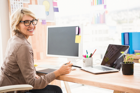 woman smile: Portrait of smiling casual designer working at her desk in the office Stock Photo