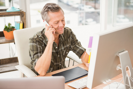 landline: Smiling casual businessman having a phone call in the office Stock Photo