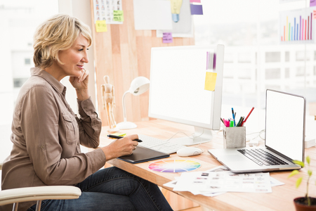 digitizer: Casual designer working at her desk in the office