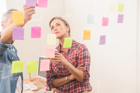 designer at work: Casual business colleagues working with sticky notes in the office Stock Photo