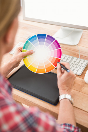 colour chart: Casual designer working with digitizer and colour chart in the office