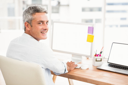 swivel: Portrait of smiling casual businessman working with computer in the office