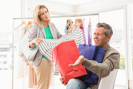complaining: Man complaining about his shopping woman in clothing store