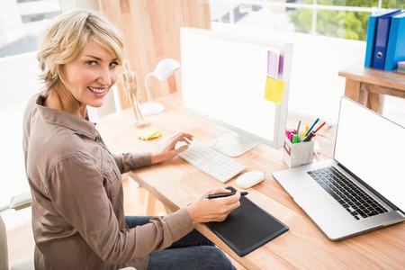 digitizer: Portrait of smiling casual designer using digitizer in the office