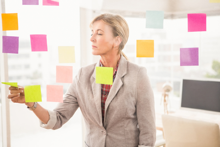 sticky notes: Casual businesswoman reading sticky notes in the office