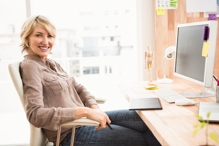 woman smile: Portrait of smiling casual designer sitting at desk in the office