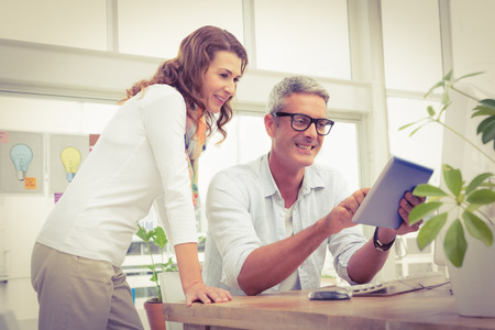 career: Two smiling casual designers working with tablet in the office Stock Photo