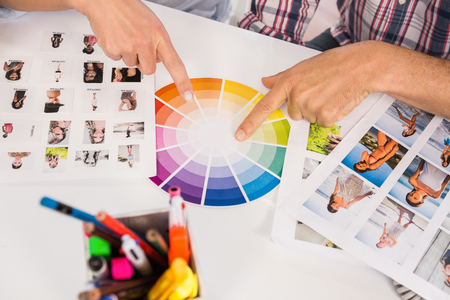 colour chart: Casual designers working with colour chart and photographs in the office Stock Photo