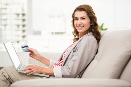 woman on couch: Portrait of casual businesswoman sitting on couch and ordering online in the office