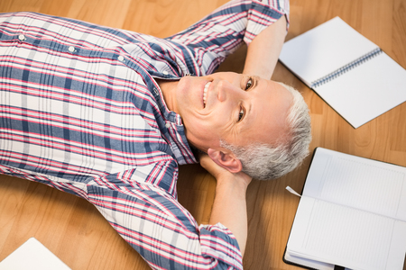 articulos oficina: Retrato de hombre sonriente acostado en el piso rodeado de art�culos de oficina
