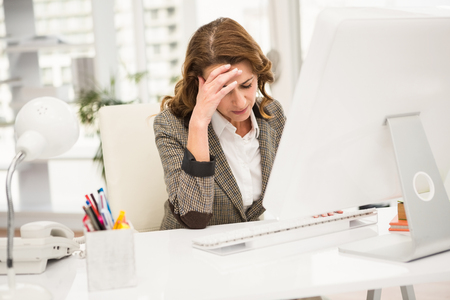 Overworked casual businesswoman working with computer in the office Stock Photo