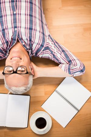 articulos de oficina: Retrato de hombre sonriente acostado en el piso rodeado de artículos de oficina