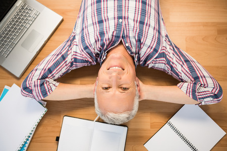 surrounded: Portrait of smiling man lying on floor surrounded by office items