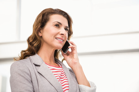 on call: Casual businesswoman having a phone call in the office Stock Photo
