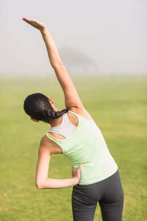 parkland: Rear view of sporty woman stretching arms in parkland