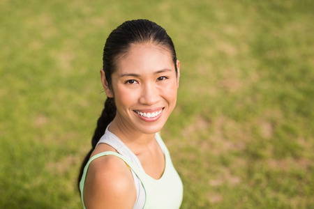 parkland: Portrait of smiling sporty woman looking at camera in parkland