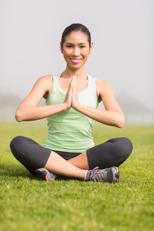 parkland: Portrait of smiling sporty woman doing yoga in parkland Stock Photo