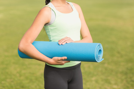 parkland: Sporty woman holding exercise mat in parkland Stock Photo