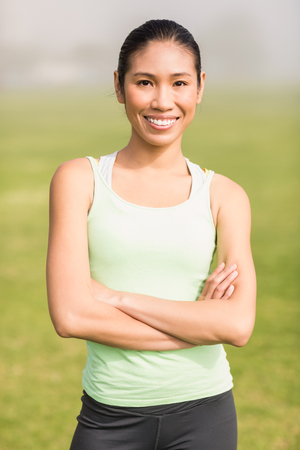 parkland: Portrait of smiling sporty woman with arms crossed in parkland