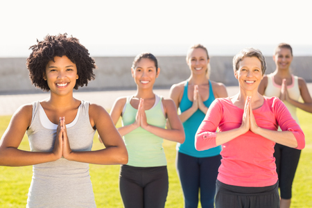 parkland: Portrait of smiling sporty women doing prayer position in yoga class in parkland