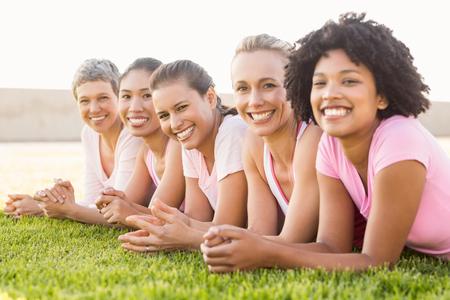 Portret van lachende vrouwen liggen in een rij en het dragen van roze voor borstkanker in een park