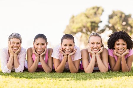 rak: Portret uśmiechnięte kobiety leżące w jednym rzędzie, a noszenie różowy raka piersi w parku