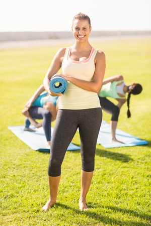 parkland: Portrait of smiling sporty brunette in front of friends doing exercises in parkland