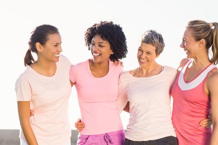 cancer de mama: Riendo las mujeres que usan de color rosa para el c�ncer de mama en un parque Foto de archivo