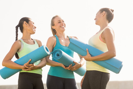 parkland: Laughing sporty women with exercise mats in parkland