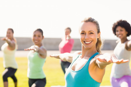 yoga: Portrait of smiling sporty blonde doing yoga in yoga class in parkland Stock Photo