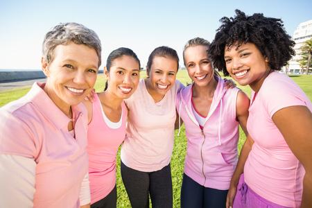 cancer de mama: Retrato de mujeres sonrientes llevando el rosa para el cáncer de mama en un parque Foto de archivo