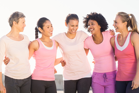 breast: Laughing women wearing pink for breast cancer in parkland Stock Photo