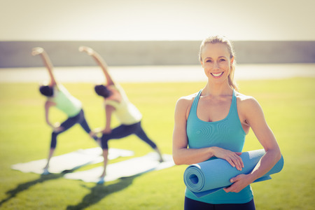 parkland: Portrait of smiling sporty blonde in front of friends doing exercises in parkland Stock Photo