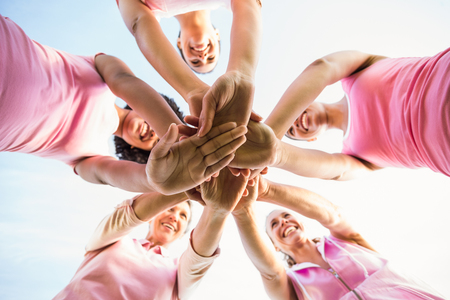 cancer de mama: Las mujeres que usan de color rosa para el c�ncer de mama y ponen las manos juntas en un parque Foto de archivo