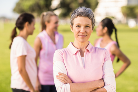 women breast: Portrait of woman wearing pink for breast cancer in front of friends in parkland