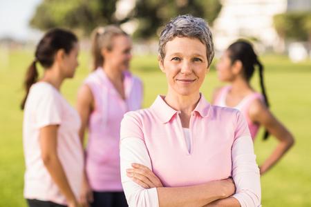 cancer de mama: Retrato de mujer que llevaba de color rosa para el c�ncer de mama en frente de amigos en un parque Foto de archivo