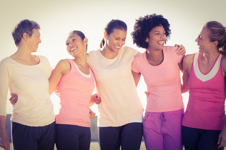 Laughing women wearing pink for breast cancer in parkland Stock Photo