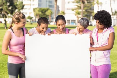 rak: Kobiety na sobie różowy raka piersi i trzymając puste plakat w parku Zdjęcie Seryjne